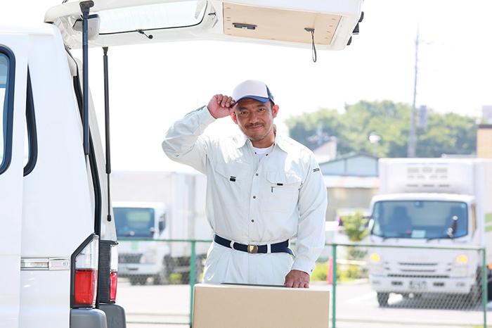 ワゴン車から荷物を下ろす爽やかなスタッフ