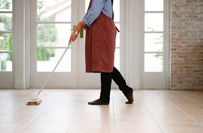 タイル張りの床を掃除するエプロン姿の女性