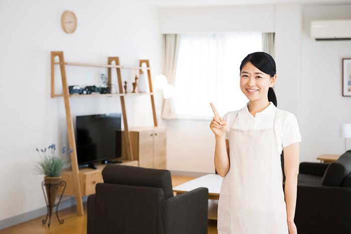 整頓された部屋に立つ笑顔の若い女性