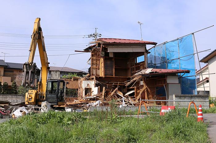 木造住宅を解体している一台の重機