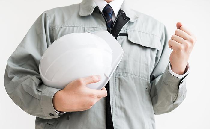 ヘルメットを片手にガッツポーズをしている作業着の男性
