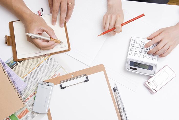 電卓やメモ帳などが広げられている机