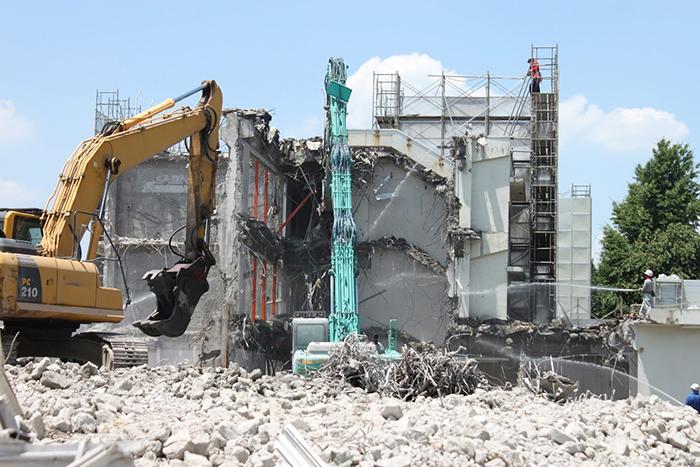 コンクリートの建物を解体している二台の重機