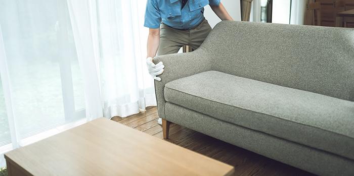 大きなソファを移動させているスタッフ