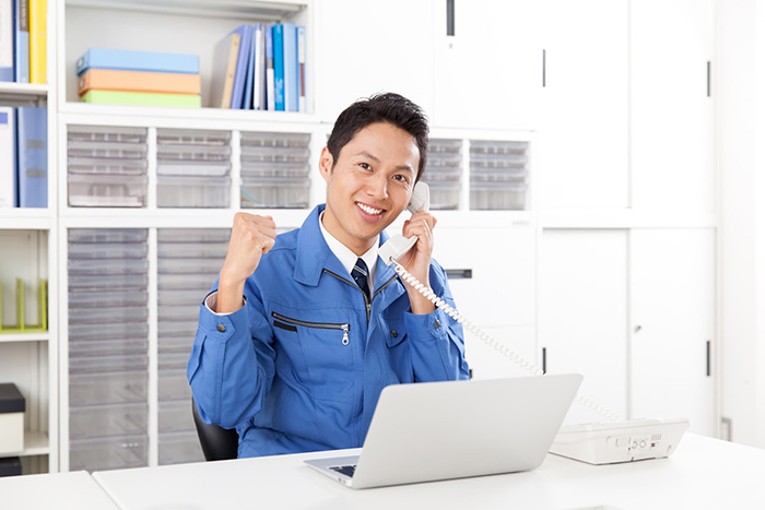 電話を片手に笑顔でガッツポーズをしている作業着の男性