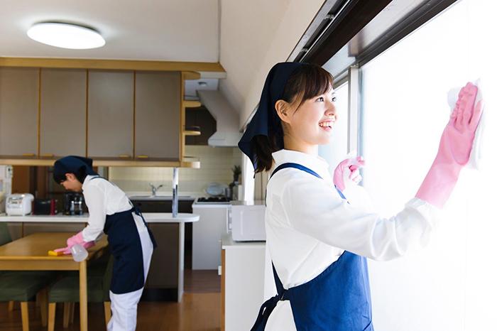 机や窓を掃除している二人の女性
